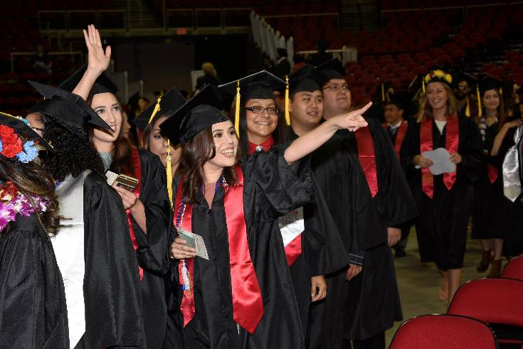 Graduates waving to the crowd